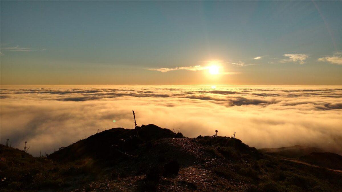 Paisaje al atardecer con nubes, sol y cerro en Ensenada, Baja California